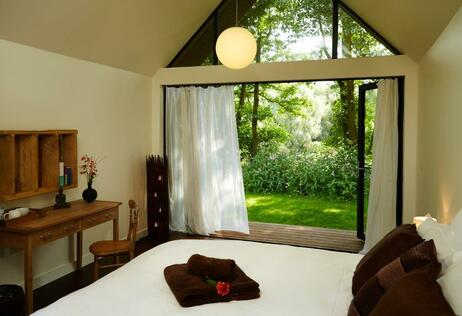 Luxurious hotel style bedroom with countryside view through large open glass doors